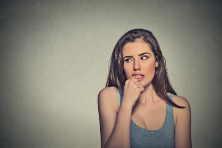 obsessive compulsive: Closeup portrait nervous looking young woman biting her fingernails craving something anxious isolated grey background copy space. Negative human emotion facial expression body language perception