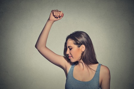Closeup portrait young woman, smelling, sniffing her wet armpit, something stinks, very bad foul odor situation isolated grey wall background. Negative human emotion facial expression feeling reaction