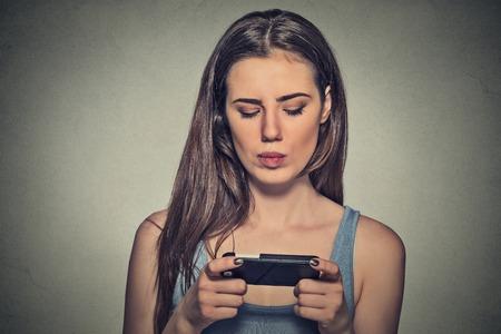 Retrato joven mujer enojada infeliz, molesto por algo, a alguien en su mensajes de texto de teléfono celular, recibir malas noticias sms mensaje de texto aislado fondo de la pared gris. Rostro humano reacción emoción expresión