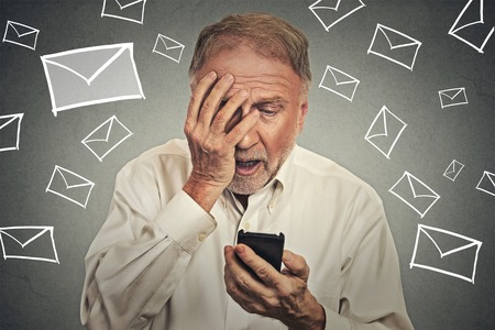 grumpy old man: Upset stressed man holding cellphone disgusted shocked with message he received isolated on gray background. Funny looking human face expression emotion feeling reaction life perception body language