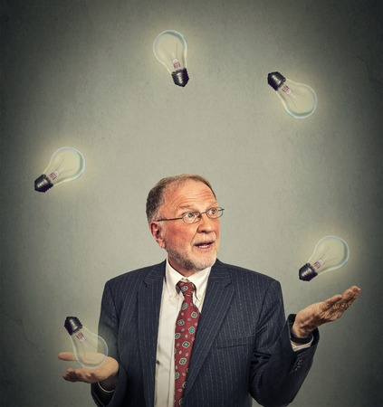 mind powers: Portrait happy senior business man executive in suit juggling playing with light bulbs isolated on gray office wall background Stock Photo