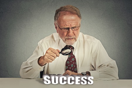 business skeptical: Skeptical look at success. Senior business man mature boss in suit looking through magnifying glass analyzing success sign Stock Photo