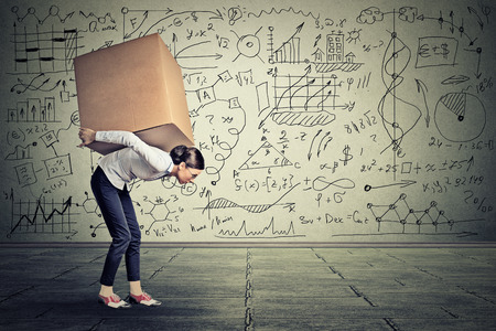 Young woman carrying heavy box walking along gray wall covered with writing of math science life ideas formulas
