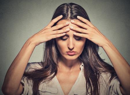 portret beklemtoonde droevige jonge vrouw met gesloten ogen te hebben slechte dag die op grijze muur achtergrond Stockfoto