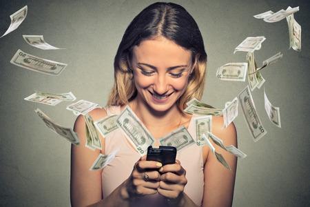 Technologie banque en ligne de transfert d'argent, e-commerce concept. Jeune femme heureuse utilisant smartphone avec billets d'un dollar battant loin de l'écran isolé sur gris office de mur de fond. Banque d'images - 43388536