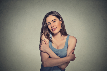 isolated on gray: Closeup portrait confident smiling woman holding hugging herself isolated gray wall background. Positive human emotion, facial expression, feeling, reaction, situation, attitude. Love yourself concept