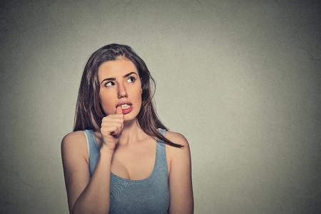 nerveux: Portrait Gros plan air nerveux jeune femme mordre ses ongles craving quelque chose anxieux gris arrière-plan copie espace isolé. Émotion humaine négative expression faciale langage corporel perception