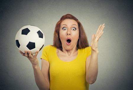 asombro: Mujer Sorpresa atónito. La mujer del retrato del primer con el balón de fútbol que parece sorprendida en plena incredulidad boca abierta aislado fondo gris de la pared. Cuerpo expresión facial emoción humana. Chica divertida