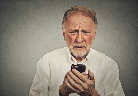 Closeup worried elderly man looking at his smart phone isolated on gray wall background