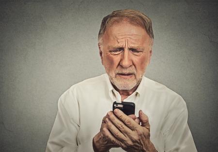 confundido: Primer anciano preocupado mirando su teléfono inteligente aisladas sobre fondo gris de la pared