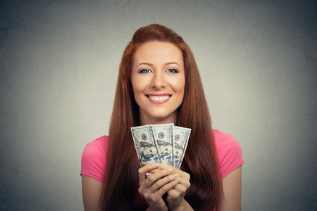 financial reward: Closeup portrait super happy excited successful young business woman holding money dollar bills in hand isolated grey wall background. Positive emotion facial expression feeling. Financial reward