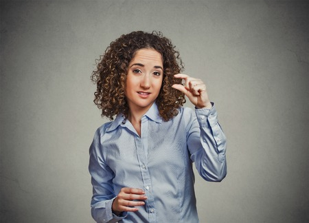 Closeup portrait skeptical young curly brown hair woman showing small amount gesture with hand fingers isolated gray wall background. Human emotion facial expression feelings body language sign symbol Imagens