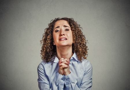 sorry: Closeup portrait young woman gesturing with clasped hands, pretty please with sugar on top, isolated gray background. Human emotion facial expression feeling, signs symbols, body language