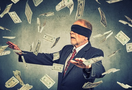 a blind: Blindfolded senior businessman trying to catch dollar bills banknotes flying in the air on gray wall background. Financial corporate success or crisis challenge concept