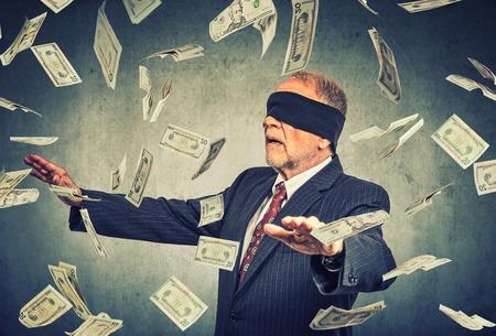 Mit verbundenen Augen älterer Geschäftsmann versucht, in der Luft auf grauen Wand Hintergrund fliegen Dollar-Scheine Banknoten zu fangen. Finanzielle Unternehmenserfolg oder Krise Herausforderung Konzept