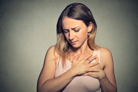 nude young woman: sick woman with heart attack, pain, health problem holding touching her chest with hands isolated on gray wall background. Human face expression