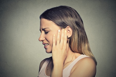 dolor de oido: Tinnitus. Perfil lateral del primer enfermo mujer joven que tiene dolor de oído tocar la cabeza dolorosa aislado en fondo azul
