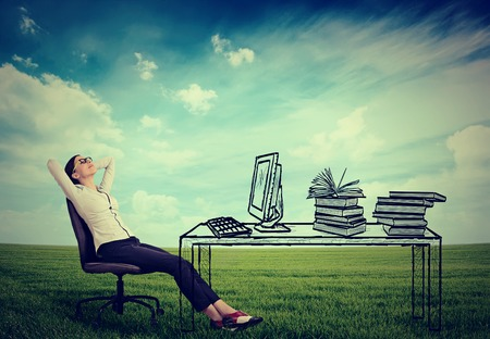 green office: young businesswoman relaxing sitting in the office in the middle of a green meadow. Stress free working environment concept