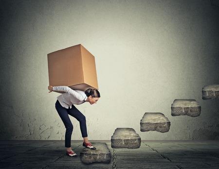 Difícil concepto perspectiva tarea. Mujer delgada joven llevando gran caja pesada en la espalda de arriba Foto de archivo - 43705090