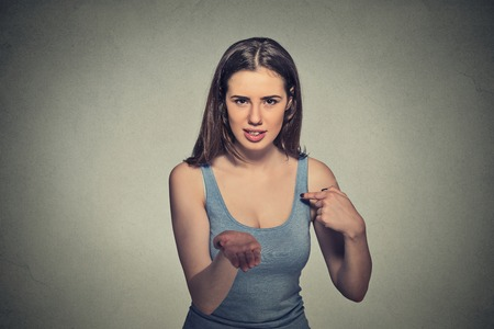 pay money: Portrait young woman gesturing with hand palms up to pay back now bills money isolated on gray wall background. Negative human emotion facial expression feeling reaction body language Stock Photo
