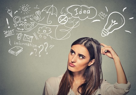 scratching head: Portrait puzzled young woman thinking scratching head has many ideas looking up isolated gray wall background. Human face expression emotion feeling life perception. Decision making process concept