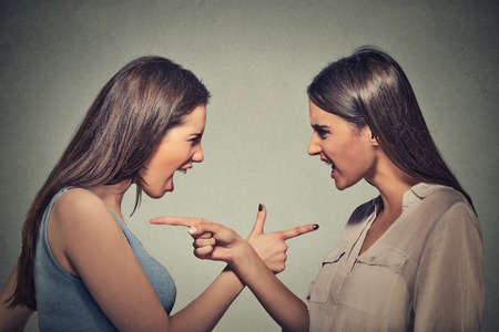 Side profile portrait two angry upset women blaming each other for something wrong isolated on gray wall background. Negative human emotion facial expression. Interpersonal conflict
