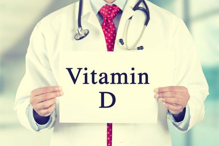 osteoporosis: Primer médico manos sosteniendo signo tarjeta blanca con el mensaje de texto de la vitamina D sobre fondo oficina Cliic hospitalaria. Imagen Filtro estilo retro Instagram