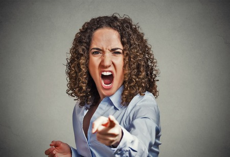 Portrait angry young woman pointing finger at camera screaming isolated on grey wall background