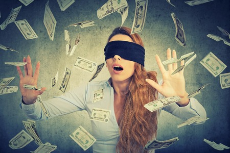 Blindfolded young entrepreneur businesswoman trying to catch dollar bills banknotes flying in the air on gray wall background. Financial corporate success or crisis challenge concept Archivio Fotografico
