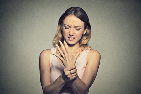 Young woman holding her painful wrist isolated on gray wall background. Sprain pain Standard-Bild