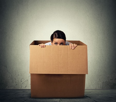 hide: Young woman hiding in a carton box