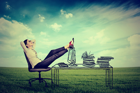 office environment: young businesswoman relaxing sitting in the office in the middle of a green meadow. Stress free working environment concept