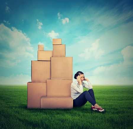 stress woman: young stressed woman sitting on the ground green grass with many boxes