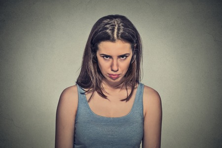 aggravated: Closeup portrait angry young woman about to have nervous atomic breakdown isolated on gray wall background. Negative human emotions facial expression feelings attitude