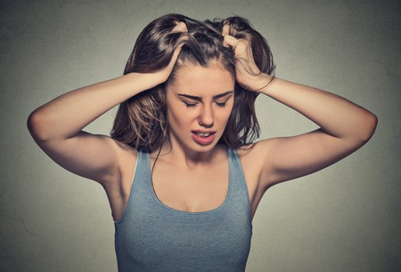 Frustrated stressed young woman. Headshot unhappy overwhelmed girl having headache bad day pulling her hair out isolated on grey wall background. Negative emotion face expression feelings perception Stock Photo