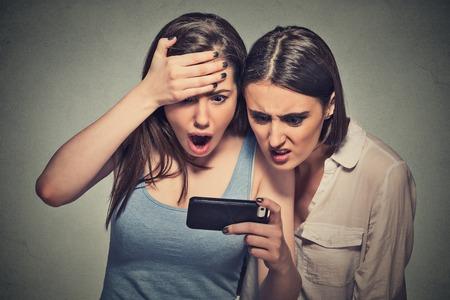 sorpresa: Dos mujeres conmocionado desagradaron chicas j�venes que miran el tel�fono m�vil de ver el mensaje de malas noticias o fotos de emoci�n desagradable en la cara aislada en el fondo gris de la pared. La emoci�n humana, la reacci�n, la expresi�n