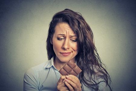 femme triste: Portrait triste jeune femme fatiguée de restrictions alimentaires craving bonbons de chocolat isolé sur fond gris mur. Visage humain expression émotion. Concept de la nutrition. Sentiments de culpabilité