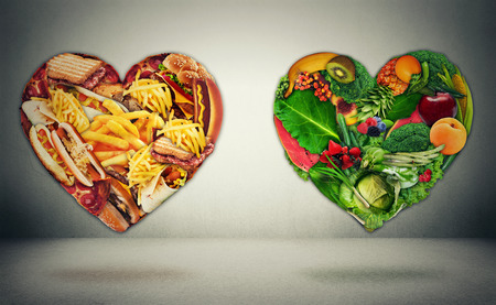 disease control: Diet choice dilemma and heart health concept. Two hearts one shaped of green vegetables fruit and alternative one made of  fatty junk high calorie food. Heart disease and food medical health care