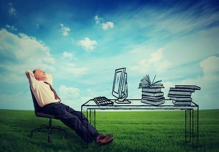 Gelukkig senior zakenman ontspannen aan zijn bureau in het midden van de groene weide in openlucht Stockfoto