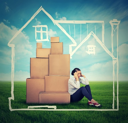 moving company: young stressed woman sitting on the ground green grass with many boxes