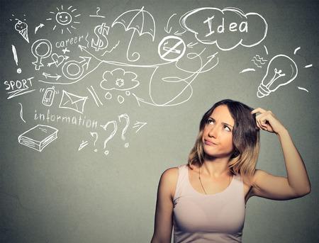gente pensando: Retrato desconcertado joven pensando rascarse la cabeza tiene muchas ideas mirando hacia arriba aislados fondo de la pared gris. Expresión de la cara humana emoción percepción vida. Concepto de proceso de toma de decisiones