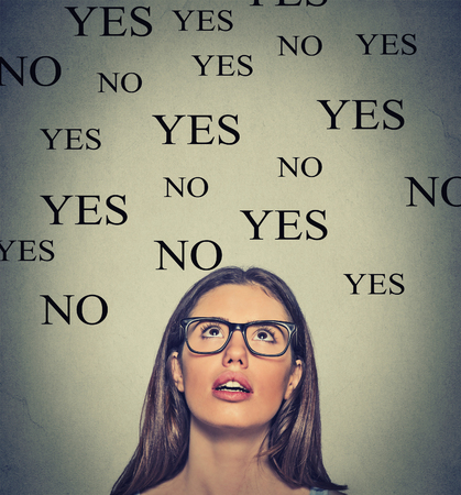 no: Thinking young woman with yes or no choice looking up on grey wall background Stock Photo