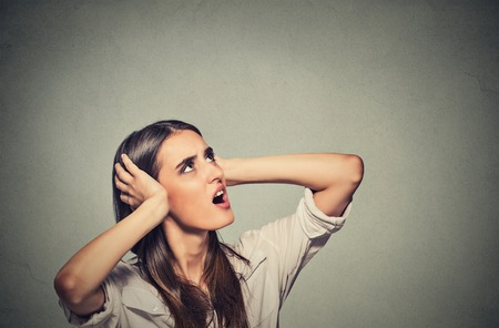 ruido: Retrato joven molesto, triste, estresado Mujer tapándose los oídos, mirando hacia arriba, por decir, dejar de hacer ruido fuerte, y me da dolor de cabeza fondo gris aislado con copia espacio. Reacción emoción negativa