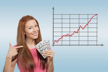 Negocios, personas y dinero concepto. Empresaria sonriente feliz con el dólar de dinero en efectivo en el fondo azul y el gráfico de divisas subiendo