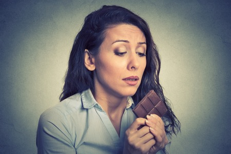good and bad: Portrait sad young woman tired of diet restrictions craving sweets chocolate isolated on gray wall background. Human face expression emotion. Nutrition concept. Feelings of guilt