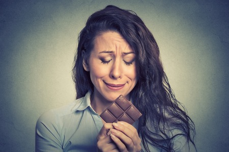restrictions: Portrait sad young woman tired of diet restrictions craving sweets chocolate isolated on gray wall background. Human face expression emotion. Nutrition concept. Feelings of guilt