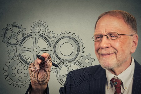 business gears: Elderly business man with gears and ideas Stock Photo