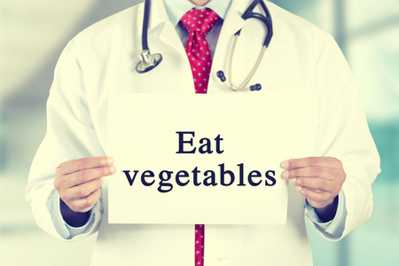 cholesterol free: Closeup doctor hands holding white card sign with eat vegetables text message isolated on hospital clinic office background.   Stock Photo