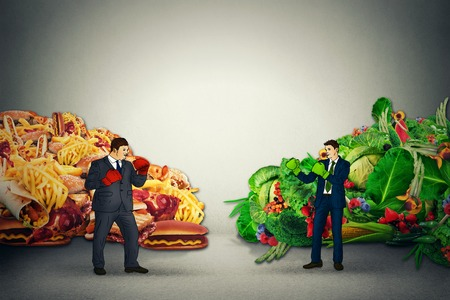 fatty food: Vegetarian food representative fighting unhealthy junk fatty food guy with boxing gloves ready to punch each other. Diet battle nutrition concept idea Stock Photo