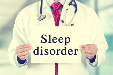 Closeup doctor hands holding white card sign with sleep disorder text message isolated on hospital clinic office background.